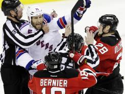 Devils players go after New York's Mike Rupp after punched New Jersey goalie Martin Brodeur in Game 4.