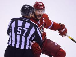 Phoenix Coyotes captain Shane Doan is restrained by linesman Jay Sharrers after Dustin Brown's overtime hit on Michal Rozsival.