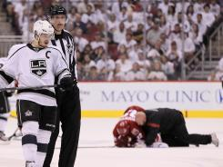 Phoenix Coyotes defenseman Michal Rozsival lies on the ice after a hit by Los Angeles captain Dustin Brown.