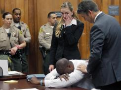 Brian Banks reacts as attorney Justin Brooks, right, and attorney Alissa Bjerkhoel stand by, as Banks' rape and kidnapping conviction was dismissed Thursday. It has been 10 years since Banks, then 16, pleaded no contest to a rape charge brought after a childhood friend falsely accused him of attacking her at their Long Beach high school.