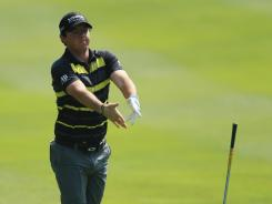 Rory McIlroy of Northern Ireland throws his club in frustration on his way to a first-round 74 at the after BMW PGA Championship.