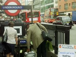 In a July 17, 2002, file photo, travellers make their way into the London underground at Chancery Lane station before the start of a 24-hour strike on the public service.