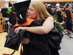 Jocelyn Leonard, the mother of late basketball player Wes Leonard, hugs one of her choir students during Fennville's commencement ceremony at Fennville High School.