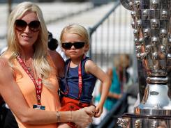 Susie Wheldon and her son, Sebastian, pose with the Borg-Warner Trophy during Saturday's drivers meeting ahead of Sunday's running of the 96th Indianapolis 500.