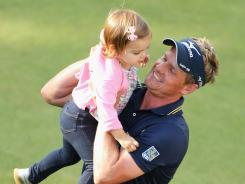 Luke Donald of England celebrates winning the BMW PGA Championship on Sunday with daughter Elle.