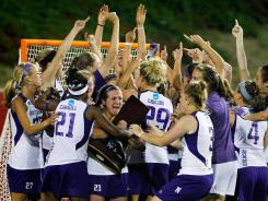 Northwestern players celebrate their 8-6 win over Syracuse in the NCAA college women's lacrosse championship. It was the Wildcats seventh title in the past eight years.