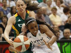 Minnesota Lynx guard Candice Wiggins (11) fights for a loose ball against Seattle Storm guard Sue Bird in the first half of Minnesota's win on Sunday.