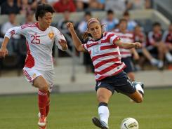 U.S. forward Alex Morgan (13) shoots the ball past China midfielder Zhang Rui (25) during their match at PPL Park in Chester, Pa., on Sunday.