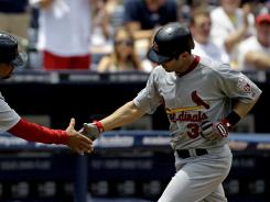 Cardinals' Daniel Descalso gets a hand shake from third base coach Jose Oquendo after hitting a two-run home run in the third inning.