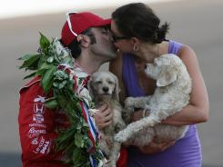 Indy 500 champion Dario Franchitti kisses his wife Ashley Judd (while they hold their two dogs Buttermilk and Shug) beside the Borg Warner Trophy.