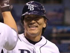 Tampa Bay Rays outfielder Hideki Matsui high-fives teammates after hitting a two-run home run in his first game since being recalled from Triple-A.