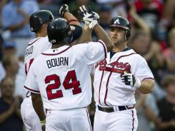 Braves second baseman Dan Uggla, right, celebrates his three-run home run with teammates Martin Prado, left, and Michael Bourn.