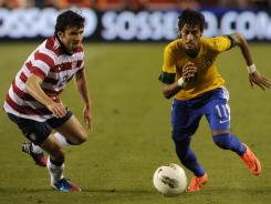 Brazil forward Neymar (11) runs past USA defender Michael Parkhurst (2). Neymar had one goal and two assists in the win.