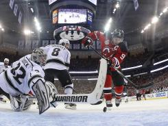 Kings goalie Jonathan Quick stops a shot by Devils captain Zach Parise in Game 1.