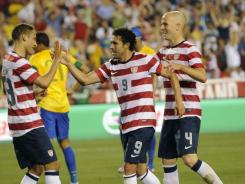 U.S. forward Herculez Gomez (9) celebrates after scoring a goal against Brazil with midfielder Fabian Johnson (23) and midfielder Michael Bradley (4) during the first half of a men's international friendly match at FedEx Field in Landover, Md., on Wednesday.
