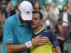 Paul-Henri Mathieu of France, right, embraces John Isner of the USA after Mathieu won the second-round French Open match on Thursday 18-16 in the fifth set.