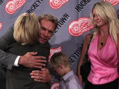 Detroit Red Wings captain Nicklas Lidstrom of Sweden hugs team owner Marian Ilitch next to his wife Annika after announcing his retirement.