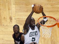 Kevin Garnett dunks the ball over Dwyane Wade and Ronny Turiaf on the way to a team-leading 24-point, 11-rebound game in the Boston Celtics' 101-91 victory Friday vs. the Miami Heat.