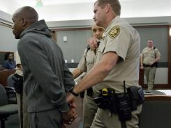 Floyd Mayweather is led away by court marshall Ron Johnson, Friday to begin an 87-day jail term for attacking his ex-girlfriend in September 2010 while two of their children watched.