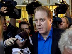 Former Boston Red Sox pitcher Curt Schilling, center, is followed by news media as he departs the Rhode Island Economic Development Corporation headquarters on May 21. Schilling's 38 Studios recently laid off its entire staff and has been trying to stay afloat.