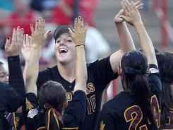 Arizona State pitcher Hillary Bach, center back, celebrates with her team after defeating LSU during the Women's College World Series in Oklahoma City, on Saturday.