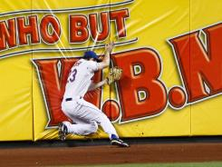 Mike Baxter makes a diving catch against the left-field wall to preserve Johan Santana's no-hit bid in the seventh inning.