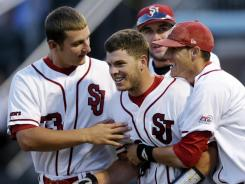 St. John's Danny Bethea (26) is congratulated by teammates Eric Peterson, left, and Pat Talbut, right, after his home run in the ninth inning against North Carolina during their NCAA regional game on Saturday in Chapel Hill, N.C. St. John's won 5-4.