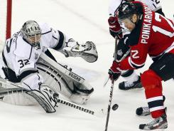 Los Angeles Kings goalie Jonathan Quick poke checks the puck away from New Jersey Devils left wing Alexei Ponikarovsky during the second period Saturday.