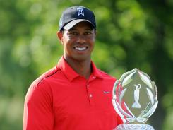 Tiger Woods holds up the trophy after winning the Memorial Tournament for a record fifth time.