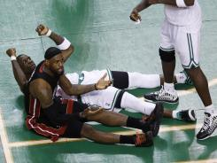 Heat forward LeBron James, sitting, looks up in disbelief after fouling out of Game 4 of the Eastern Conference finals. Celtics forward Mickael Pietrus, lying down, drew the offensive foul.