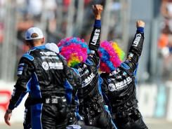 Crewmembers wearing clown wigs prepare to greet Jimmie Johnson after his victory in the FedEx 400 at Dover International Speedway. Johnson said he got a chuckle at his front-tire catcher during the race on pit stops.