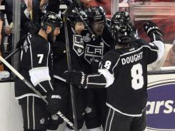 Anze Kopitar, center, and the Kings celebrate his second-period goal that helped the Kings beat the Devils 4-0.