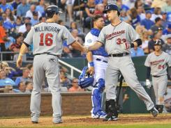Minnesota Twins first baseman Justin Morneau is congratulated by left fielder Josh Willingham after hitting a home run against the Kansas City Royals.