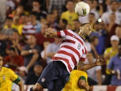 USA forward Clint Dempsey (8) leaps in the air to head the ball over Brazil defender Marcelo (6) as defender Danilo (21) looks on during the second half of a men's international friendly match.