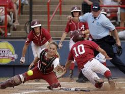 Alabama's Kaila Hunt slides home safely as Oklahoma catcher Jessica Shults tries to block the plate in the second inning of the second game of the NCAA Women's College World Series.