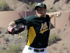 Former first base prospect Sean Doolittle throws during a spring training session Feb. 27 in Phoenix. The A's promoted the reliever to the big leagues Monday.