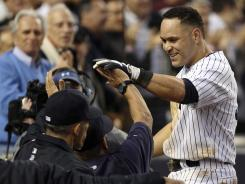 The Yankees' Russell Martin, right, is greeted by coaches and teammates at the dugout after hitting a grand slam in the fourth inning.