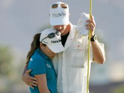 I.K. Kim of South Korea gets a hug from her caddie after missing a putt on the 72nd hole that would have won her the Kraft Nabisco Championship. Kim has moved on and is not dwelling on it.