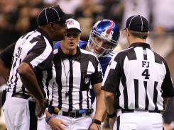 Will Giants QB Eli Manning and Co. be overseen by referees like Ed Hochuli, center, in 2012 or replacement crews?