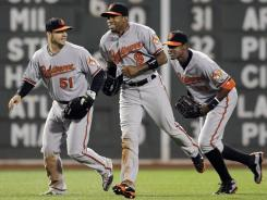 Orioles outfielders Steve Pearce, left, Endy Chavez, center, and Adam Jones celebrate on the field after the Orioles defeated the Red Sox 8-6 in 10 innings.
