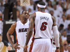 Miami guard Dwyane Wade (3) talks to LeBron James (6) during the first half of the Heat's Game 5 loss to the Celtics.