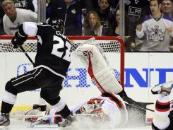 New Jersey Devils goalie Martin Brodeur stops an attempt by Los Angeles Kings center Trevor Lewis in the third peroid on Wednesday.