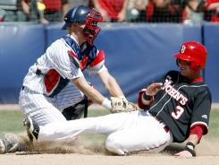 Arizona's Riley Moore tags out St. John's Sean O'Hare in the ninth inning during their NCAA college baseball super regional game.