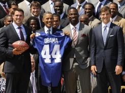 New York Giants linebacker Chase Blackburn (far left), United States president Barack Obama (middle left), defensive end Justin Tuck (middle right) and quarterback Eli Manning (far right) pose with a jersey during a visit by the New York Giants to the White House on Friday.