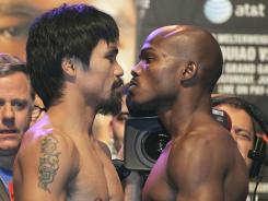 Manny Pacquiao, left, and Timothy Bradley face off after weighing in Friday for Saturday's WBO welterweight title fight in Las Vegas.