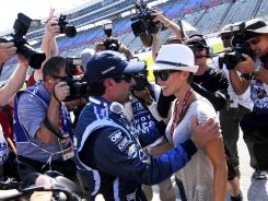 Alex Tagliani celebrates with his wife, Bronte, after earning the pole position for Saturday's Firestone 550.