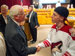 Former San Jose Sharks chief executive Greg Jamison, left, shakes hands with Coyotes fan Mitch Thomas, right, during a break from a special meeting to vote on a deal for the Phoenix Coyotes on Friday.