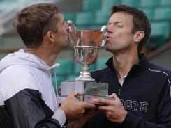 Max Mirnyi of Belarus left and Daniel Nestor of Canada kiss the trophy after winning the men's doubles final.