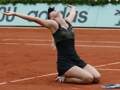 Maria Sharapova celebrates on the clay of Roland Garros after beating Sara Errani 6-3, 6-2 to win her first French Open title and complete a career Grand Slam.
