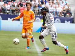 Dynamo defenseman Bobby Boswell, left, and Whitecaps forward Darren Mattocks battle for the ball during the first half of their game.